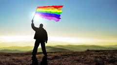Successful silhouette man winner waving Gay homo flag on top of the mountain  - stock footage