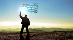 Successful silhouette man winner waving Greece flag on top of the mountain pe Stock Footage