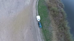 Aerial down fly. Car with  caravan ,trailer on  dirt road. Travel symbol Stock Footage