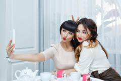 Girlfriends doing selfie. Tea party. - stock photo