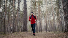 Man running in forest woods training and look at smart watches. Stock Footage