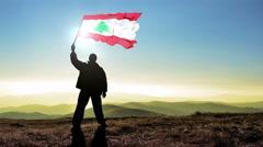 Successful silhouette man winner waving Lebanon flag on top of the mountain - stock footage