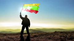 Successful silhouette man winner waving Myanmar flag on top of the mountain p Stock Footage