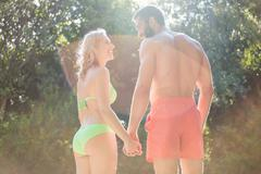 Happy couple in swimwear holding hands and smiling Stock Photos