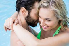 Couple embracing in swimming pool Stock Photos