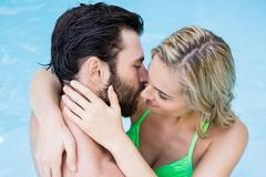 Romantic couple embracing in swimming pool Stock Photos