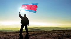 silhouette man winner waving North Korea flag on top of the mountain - stock footage