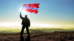 Successful silhouette man winner waving Norway flag on top of the mountain pe Stock Footage
