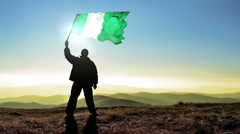 Successful silhouette man winner waving Nigeria flag on top of the mountain p Stock Footage