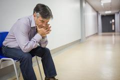 Thoughtful professor sitting on chair Kuvituskuvat