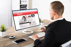Young Businessman Reading News On Computer At Office Stock Photos