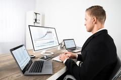 Young Stock Market Broker Looking At Graphs On Computer In Office - stock photo