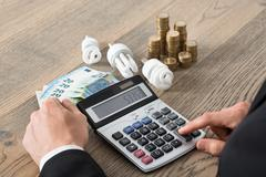 Close-up Of Businessman Using Calculator With Fluorescent Bulb And Coins On D - stock photo