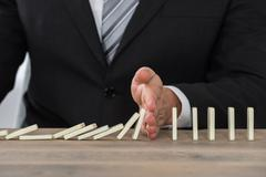 Close-up Of A Businessman Hand Stopping Dominoes From Falling On A Desk In Of Stock Photos