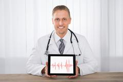 Close-up Of Young Happy Male Doctor Showing Heartbeat On Digital Tablet At De Stock Photos