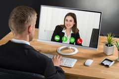 Young Businessman Video Conferencing With Colleague On Laptop At Desk In Offi Kuvituskuvat