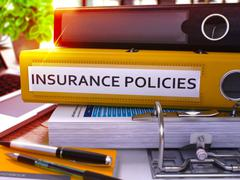 Insurance Policies on Yellow Ring Binder. Blurred, Toned Image - stock illustration