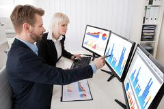 Two Young Businesspeople Analyzing Graph On Multiple Computer At Office - stock photo
