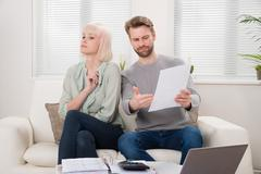 Unhappy Couple Having Argument Over Bill At Home - stock photo