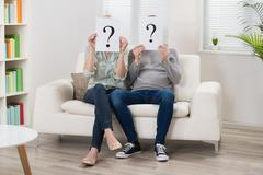 Couple Sitting On Sofa Holding Question Mark Sign In Front Of Face - stock photo