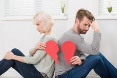 Sad Couple Sitting Back To Back Holding Red Broken Heart - stock photo