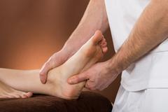Close-up Of A Woman Receiving Foot Massage From A Male Therapist At A Beauty  - stock photo