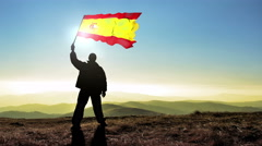 Successful silhouette man winner waving Spain flag on top of the mountain pea Stock Footage