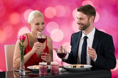 Portrait Of A Young Couple Having Dinner In A Restaurant In Bokeh Background Stock Photos