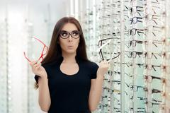 Woman Choosing Eyeglasses Frames in Optical Store - stock photo