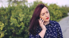 Woman talking on cellphone in the park and looking at the camera with smile. - stock footage