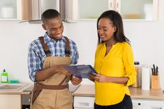 Young Happy African Handyman And Woman Looking At Clipboard Stock Photos