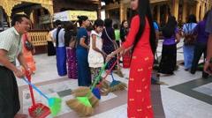 People in ceremony with brooms at Shwedagon Pagoda. Yangon, Myanmar Stock Footage
