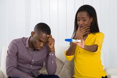 Unhappy Young African Couple Looking At Pregnancy Test Stock Photos