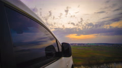 The flow of cloud against the sunset near the car. Time lapse Stock Footage