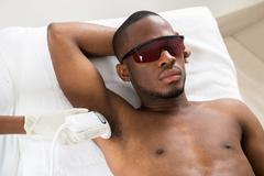 Therapist Giving Laser Epilation Treatment On Young African Man's Armpit - stock photo