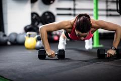 Determined woman doing push ups with dumbbell Stock Photos