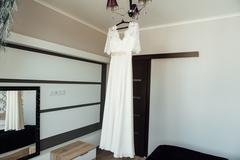 Beautiful White Wedding Gown Hanging by Window - stock photo