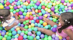 Baby girls in ball pool Stock Footage