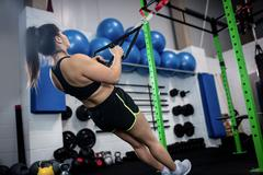 Woman doing suspension training with trx fitness straps Stock Photos