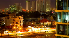 Zoom out view of streets and office buildings at night in Ho Chi Minh City Stock Footage