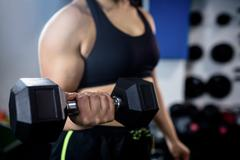 Woman exercise with dumbbells and working on her biceps Stock Photos