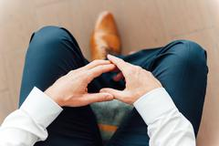 man sits with hands clasped - stock photo