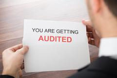 Close-up Of Businessman Opening Audit Letter In Office - stock photo