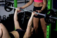 Trainer assisting a woman to lift the barbell Stock Photos