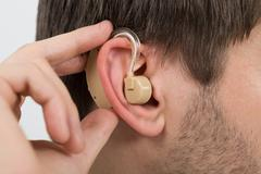 Close-up Of Man Wearing Hearing Aid In Ear Stock Photos