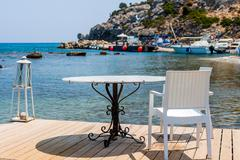 Tables with chairs in traditional Greek tavern in Kolympia town - stock photo