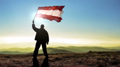 Successful silhouette man winner waving Austria flag on top of the mountain p Stock Footage
