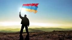 Successful silhouette man winner waving Armenia flag on top of the mountain Stock Footage