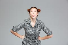 Amusing cute young woman showing tongue and making funny face Stock Photos