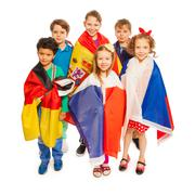Top view of kids wrapped in European nations flags - stock photo